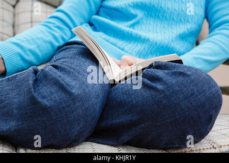 A senior woman retiree wearing blue denim jeans sits on a chair reading with a book resting on her knees indoors - Stock Photo