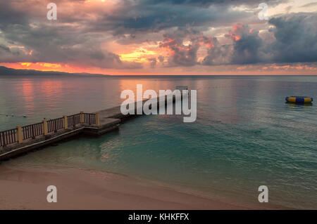 Caribbean beach and pier at sunset - Stock Photo