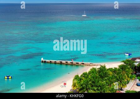 Caribbean beach and pier in Montego Bay, Jamaica island - Stock Photo