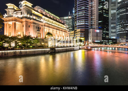 Singapore - October 6, 2017: The lights of the famous Fullerton hotel reflect in the Singapore river in front of - Stock Photo