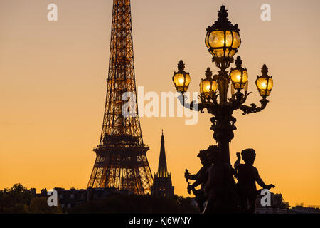 Alexandre III Bridge lamp post silhouette contrasting with the Eiffel Tower at sunset. Paris, France - Stock Photo