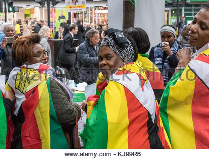London, UK. 22nd Nov, 2017. Women wrap themselves in Zimbabwe flags outside Zimbabwe House on The Strand in London, - Stock Photo