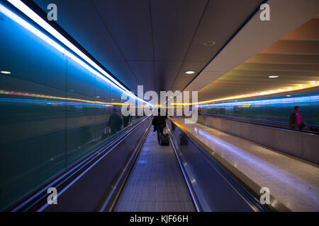 Lit moving walkway with blue and orange lights in London Heathrow Airport - Stock Photo