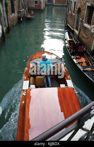 A motor boat taxi passing by in a narrow venice canal in Italy - Stock Photo
