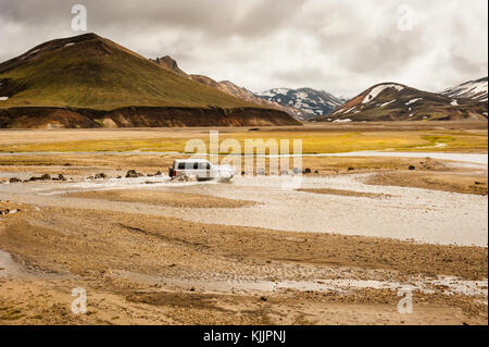 4x4 vehicle, SUV crossing a stream with Landmannalaugar colourful mountains still covered with snow, beginning of - Stock Photo