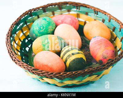 Funny Colorful Easter eggs hand painted by kids in basket on green pastel background - Stock Photo