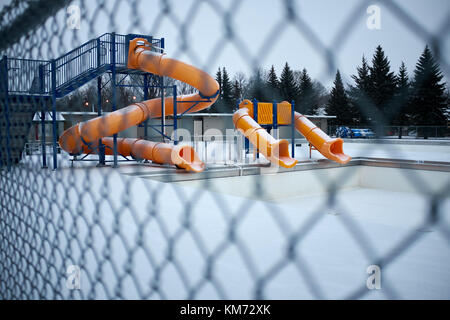 Three yellow slides at a water park leading to an emptied pool in winter with snow on the ground viewed through - Stock Photo
