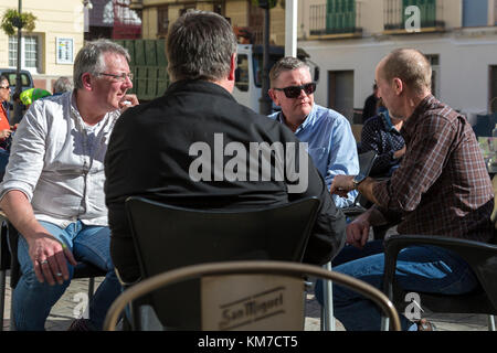 Group of 4 middle age men talking at a cafe table in Malaga Spain - Stock Photo