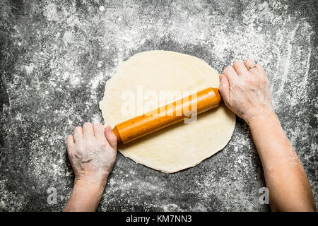 Dough background. The rolling of the hands of women for cookies. On rustic background. - Stock Photo