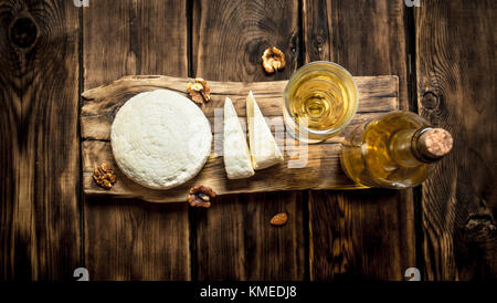Sheep cheese with white wine and walnuts. On a wooden table. - Stock Photo