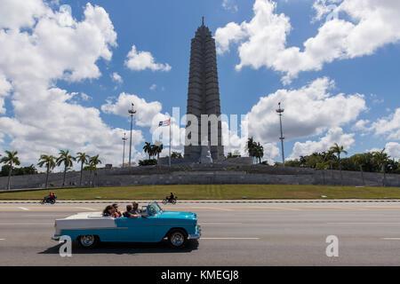 Tourists take a classic car ride by Plaza de la Revolución in Havana,Cuba. - Stock Photo