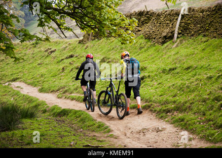 Mountain Bikers on path in Peak District National Park - Stock Photo