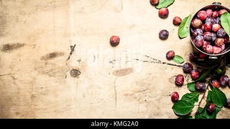 Fresh plums with green leaves. On wooden background. - Stock Photo