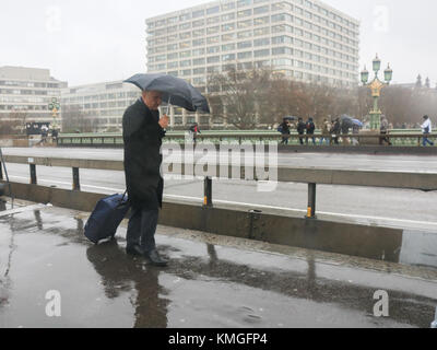 London UK. 7th December 2017. Pedestrians on Westminster are caught in  lashing rain and wind gusts as storm Caroline - Stock Photo