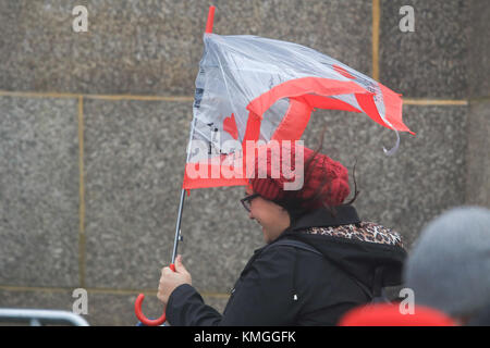 London UK. 7th December 2017. A pedestrian on Westminster Bridge struggles with an umbrella in  lashing rain and - Stock Photo