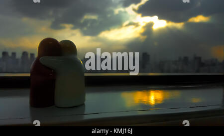 TWO OF US. Two hugging figurines on window sill facing rays of sunlight shining through clouds with skyscraper skyline. - Stock Photo