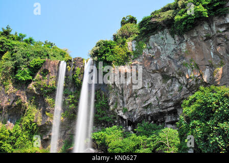 Low shot of majestic waterfall thundering down into a creek from a high cliff. Suitable for concepts such as zen - Stock Photo