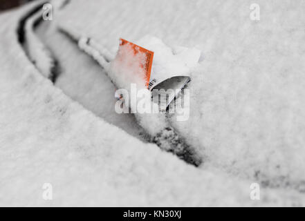 Parking violation ticket on snow covered car windshield - Stock Photo