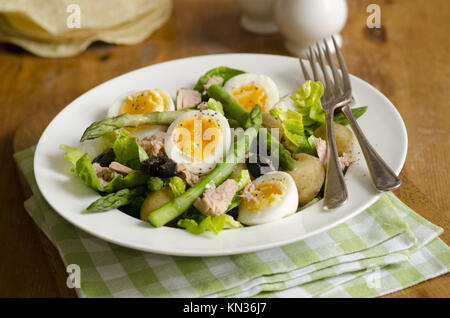 Salad made of tuna, boiled eggs, potatoes, asparagus and black olives. - Stock Photo