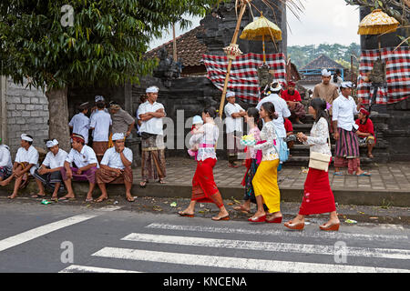 People wearing traditional Balinese clothing in front of a local temple near Bugbug village. Karangasem Regency, - Stock Photo