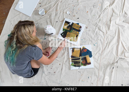 Overhead view of female artist crouching on dust sheet painting abstract canvas - Stock Photo