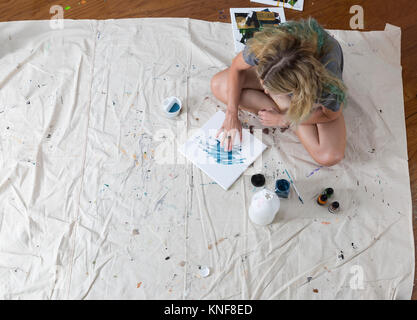 Overhead view of female artist sitting on dust sheet finger painting abstract canvas - Stock Photo
