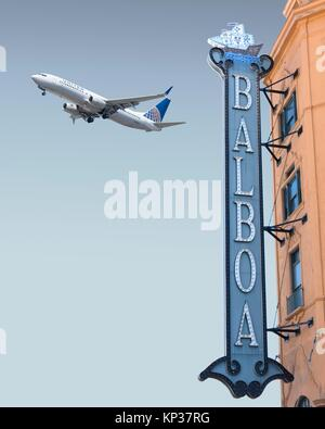 Vintage theater sign in downtown San Diego, CA, with a jet airliner taking off in the background - Stock Photo