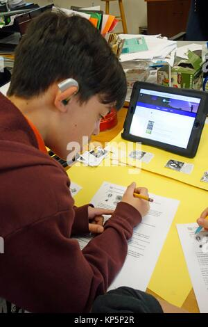 6th Grade Boy With Hearing Aid Using iPad for Science Research, Wellsville, New York, USA. - Stock Photo