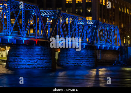 Blue Bridge at night, reflecting off the Grand River in Grand Rapids, Michigan, USA - Stock Photo