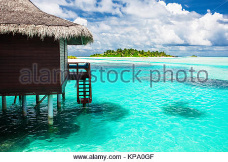 Over water bungalow with steps into amazing blue lagoon with island - Stock Photo