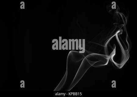 A whisp of white smoke against the black background - Stock Photo