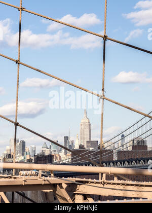 NEW YORK, USA - JANUARY 5, 2015: The Empire State Building shines in the afternoon seen from the Brooklyn Bridge. - Stock Photo