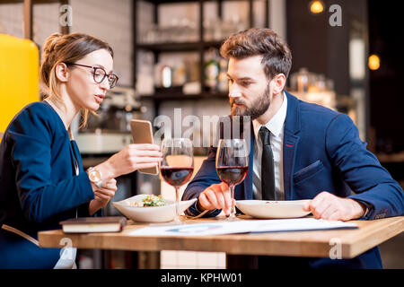 Caucasian business couple dressed strictly in the suits working together with smart phone sitting at the restaurant - Stock Photo