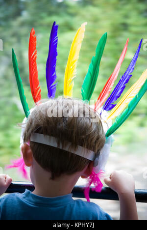 rear shot of young boy looking out of moving train's window with his head adorned with colourful feather headress - Stock Photo