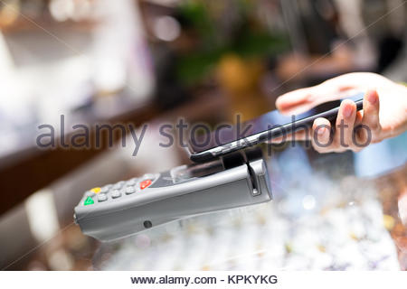 Woman paying through smartphone using NFC technology - Stock Photo