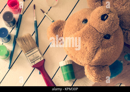 Teddy bear lying on wooden background with tempera paints and paint brushes - Stock Photo