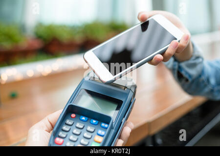 Accepting payment from customer through NFC - Stock Photo