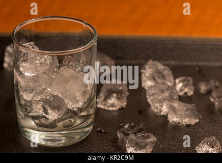 Empty Glass With Ice Cubes on Black Tray - Stock Photo