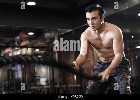 Young men exercise at the gym - Stock Photo