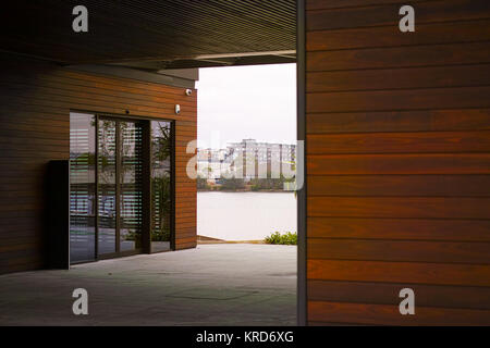 Modern wooden building exterior closeup with walkway passage to riverfront. Contemporary community architecture - Stock Photo