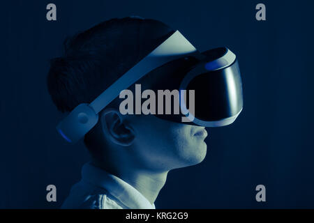 Young man plays in computer game with VR helmet and lighted from the screen. Toned. - Stock Photo