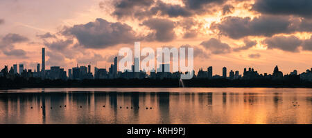A pink winter sunset over Hell's Kitchen and Midtown with the buildings reflected in the Jaqueline keneddy Onassis - Stock Photo