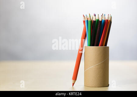 Pencils in a container on a wooden table. Accessories for drawing in a paper mug on a wooden drawing table. White - Stock Photo
