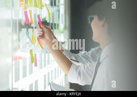 businessman putting his ideas on paper note a presentation in conference room. Focus in hands with marker pen writing. - Stock Photo