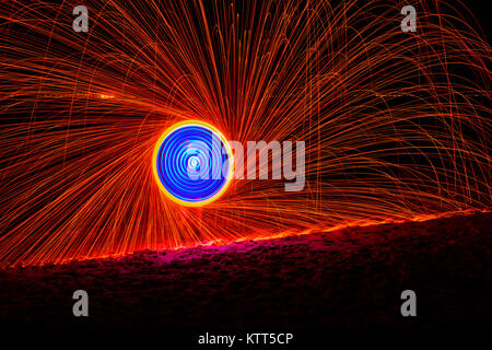 Man fire dancing with steel wool - Stock Photo
