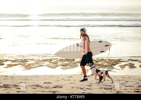 Surfer in reef boots with surfboard and helmet running jogging on the beach with his dog at sunset in Bali, Indonesia. - Stock Photo