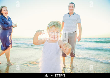 Laughing Baby girl running forward with smiling parents on the background. Happiness and harmony in family life. - Stock Photo