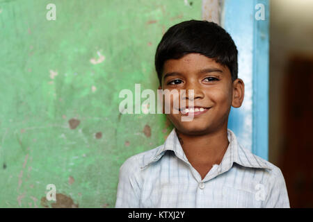 Portrait of a smiling young indian boy in a shirt in front of a green wall in his home, village near Pushkar, Rajasthan, - Stock Photo
