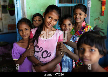 Happy indian kids holding each other in front of their house in a village near Pushkar, Rajasthan, India. - Stock Photo