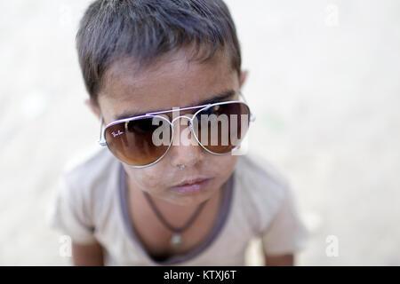 Small indian boy wearing oversized sunglasses, Village near Pushkar, Rajasthan, India. - Stock Photo